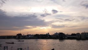 Bangkok city skyline,  Timelapse, Beautiful sunset over Chao Phraya River skyline, Sunset sky background, Long tail boat running o. River view in Thailand stock video