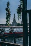 Bangkok, 12 14 18: De barkaskapitein controleert zijn barkas in de Rivier Wat Arun Temple op de achtergrond royalty-vrije stock foto