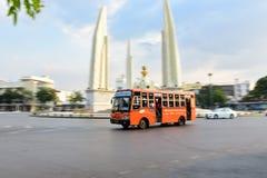 Bangkok - 4 de febrero, tráfico alrededor del monumento de la democracia durante el día Mini autobús anaranjado delante de la esc imágenes de archivo libres de regalías