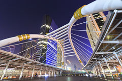 Sathorn bridge. BANGKOK - Dec 27: Night view of high buildings and public sky walk for transit between Sky Transit and Bus Rapid Transit Systems at Sathorn Royalty Free Stock Image