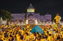 BANGKOK - DECEMBER 5: Det thailändska folket sitter utanför för att fira för den 85. födelsedagen av HMEN konungen Bhumibol Aduly Royaltyfri Bild