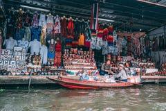 Bangkok, 12 11 18: Dos vendedores hablan el uno al otro y las mercancías del exchangig Mercado flotante de Saduak fuera de Bangko imagenes de archivo