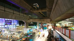 Bangkok downtown busy traffic, time lapse at night. Bangkok downtown busy traffic at Siam center, people walking to subway, time lapse at night stock video