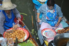 Bangkok Floating Market. In Thailand, Asia  - boats piled high with tropical fruit and vegetables, fresh, ready-to-drink coconut juice and local food cooked Royalty Free Stock Photo