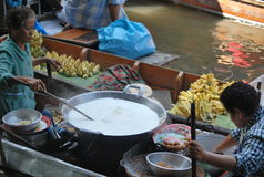 Bangkok Floating Market. In Thailand, Asia  - boats piled high with tropical fruit and vegetables, fresh, ready-to-drink coconut juice and local food cooked Royalty Free Stock Photography