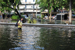 Bangkok Floods. A woman wades through a flooded street in Pinklao district on November 4, 2011 in Bangkok, Thailand. Approximately a fifth of the Thai capital is Stock Images