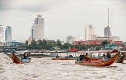 BANGKOK - JULI 2008: Stadsbyggnader över floden Chao Phraya bankade arkivbild