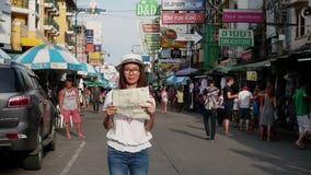 BANGKOK - JULI 16: Timelapsemening van Aziatische toerist met kaart in haar handtribune alleen met velen nationale toerist bij de stock footage