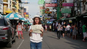 BANGKOK - JULY 16 : Timelapse view of asian tourist with map in her hand stand alone with many national tourist at Khao San road stock footage