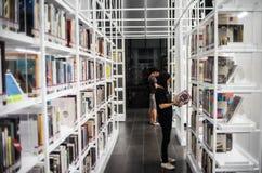 Bangkok - Juni 5,2017: Die Jugendliche steht, um ein Buch am weißen Bücherregal an TCDC-Bibliothek zu lesen Stockbild