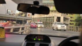 BANGKOK - JUNI 9: Motorvägsikt från passagerareplats i taxi Bilinstrumentbräda och våt vindruta från en hällregn i a arkivfilmer