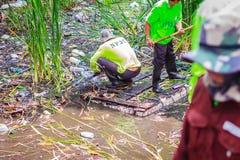 Bangkok kommunal personal i kanal som muddrar arbete för att dumpa vegetatio Fotografering för Bildbyråer