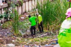 Bangkok kommunal personal i kanal som muddrar arbete för att dumpa vegetatio Royaltyfri Foto