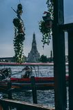Bangkok, 12.14.18: Longboat Captain controls his longboat in the River. Wat Arun Temple in the background. royalty free stock photo