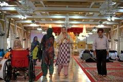Sikh people pray inside Gurudwara Siri Guru Singh Sabha temple Stock Photography