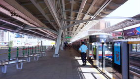 Bangkok metro Sky Train Station. people getting off at the station with the guard watching stock video
