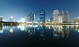 Bangkok-Nachtlandschaft von den Seeuferwolkenkratzern, die über glattes Seewasser in schönem Benjakiti-Park nachdenken Stockfotos