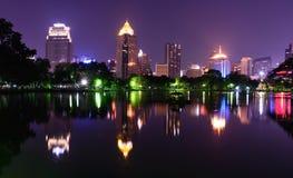 Bangkok natthorisont och vattenreflexion med den stads- sjön i sommar Arkivfoton