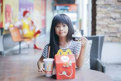 BANGKOK - OCTOBER 10 : an asian girl ,in soft focus, showed her happy meal food and toy at McDonald`s restaurant Stock Photos