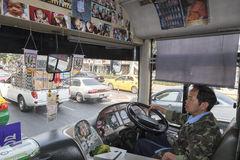 Bangkok public buses. Public buses in Bangkok are one of the kind. Every one is different. All drivers redesign them in their own style. Driver on the picture stock photography
