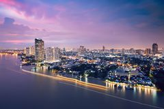Bangkok skyline during dusk. Bangkok during dusk. City skyline with traffic boats in blurred motion on the Chao Phraya River Stock Image