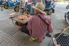 BANGKOK, TAILAND - 23 MAGGIO 2015: Uomo asiatico che vende le uova al mercato a Bangkok fotografie stock