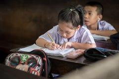 BANGKOK TAILANDIA - 23 agosto 2017: La ragazza dello studente sta studiando molto il concentrato Fa il compito nell'aula a Wannaw Immagine Stock