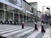 BANGKOK, TAILANDIA - 16 APRILE 2018: Donne in attrezzature religiose con l'annuncio di iPhone X nei precedenti fotografie stock libere da diritti