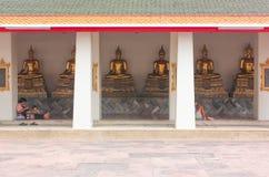 Bangkok, Tailandia - 29 aprile 2014 La gente che riposa e che prega davanti alle sculture dorate di Buddha a Wat Pho, Bangkok immagini stock libere da diritti