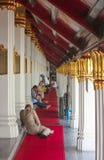 Bangkok, Tailandia - 29 aprile 2014 Uomo accanto ad un gruppo di persone che riposano a Wat Phra Kaew, tempio di Emerald Buddha immagini stock
