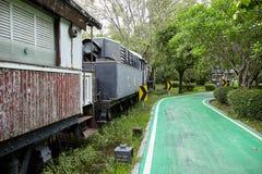 BANGKOK, TAILANDIA - 7 APRILE 2018: Vecchio treno abbandonato decorato nel parco con il vicolo verde della bici fotografia stock