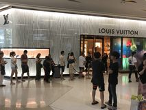 BANGKOK, TAILANDIA - 16 DE ABRIL DE 2018: Tienda de Louis Vuitton con una cola de la gente chenese asiática en un día ordinario foto de archivo