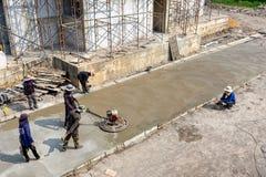 BANGKOK, TAILANDIA - 19 DE DICIEMBRE: El grupo no identificado de trabajadores del contruction aplana el cemento en el emplazamie imagen de archivo