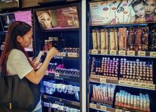 BANGKOK, TAILANDIA - 16 DE DICIEMBRE: Tiendas asiáticas no identificadas de la mujer en la sesión cosmética de BigC Petchkasem ad fotos de archivo libres de regalías