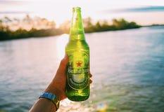 BANGKOK0, TAILANDIA - 2 DE ENERO DE 2019: botella dada de cerveza fría de Heineken en el marrón oscuro bacony con descenso del ag fotos de archivo