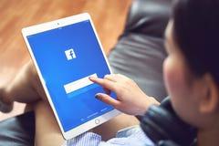 Bangkok, Tailandia - 31 de enero de 2018: la mano está presionando la pantalla de Facebook en el ipad favorable, medio social de  foto de archivo libre de regalías