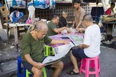 Bangkok, Tailandia - 28 de junio de 2015: Viejos hombres que leen el periódico en una parada del té en la calle de Bangkok Fotografía de archivo libre de regalías