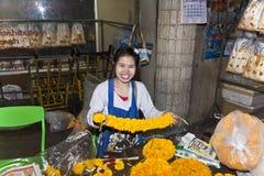 Mujer que vende las flores frescas en el mercado de la mañana en Bangkok Imagen de archivo libre de regalías
