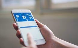 Bangkok, Tailandia - 5 de noviembre de 2018: la mano está presionando la pantalla de Facebook en el iphone 6 de la manzana fotos de archivo