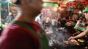 Bangkok, Tailandia - 24 de noviembre de 2018: Un cocinero cocina la comida en un restaurante del calle-lado en Chinatown metrajes