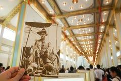 Bangkok, Tailandia - 10 de noviembre de 2017: Visitante que sostiene la postal en la exposición real del crematorio de rey Bhumib Fotografía de archivo libre de regalías