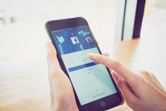Bangkok, Tailandia - 2 gennaio 2018: la mano sta premendo lo schermo di Facebook sulla mela iphone6, media sociali sta usando fotografia stock