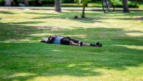 BANGKOK, TAILANDIA - 15 GIUGNO: L'uomo non specificato prende un pelo di pomeriggio sull'erba di Sri Nakhon Khuean Khan Park a Ba immagini stock libere da diritti