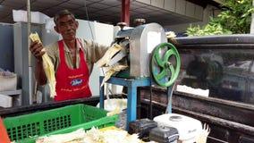 Bangkok, Tailandia - 2019-03-17 - hombre utiliza la máquina para exprimir a Sugar From Sugar Cane almacen de video