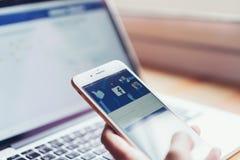 Bangkok, Tailandia - 24 luglio 2018: la mano sta premendo lo schermo di Facebook sulla mela iphone6 fotografia stock libera da diritti