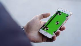 Bangkok, Tailandia 24 ottobre 2016: Smart Phone tenuto a mano Chiave verde di intensità dello schermo Fine in su Inseguimento del stock footage