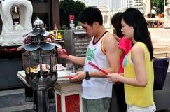 Bangkok, Tailandia: Palillos del incienso de la iluminación de los pares Imagenes de archivo