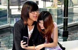 Bangkok, Tailandia: Pares adolescentes con el teléfono móvil Imágenes de archivo libres de regalías