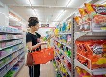 BANGKOK TAJLANDIA, KWIECIEŃ, - 14: Bezimienna kobieta robi zakupy dla Lay frytek w nawie 7-Eleven dogodny sklep na Petchkasem obrazy royalty free