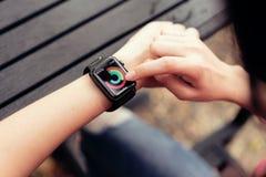 Bangkok Tajlandia, Kwiecień, - 03, 2018: kobieta dotyka ekran na sprawdzać aktywność app na Jabłczanym zegarku Obrazy Stock